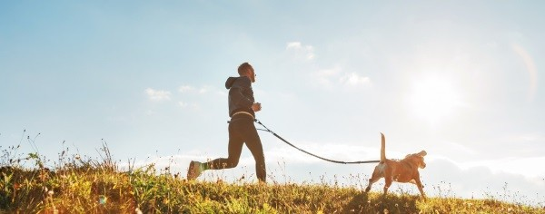 A dog owner exercising outdoors with his Beagle