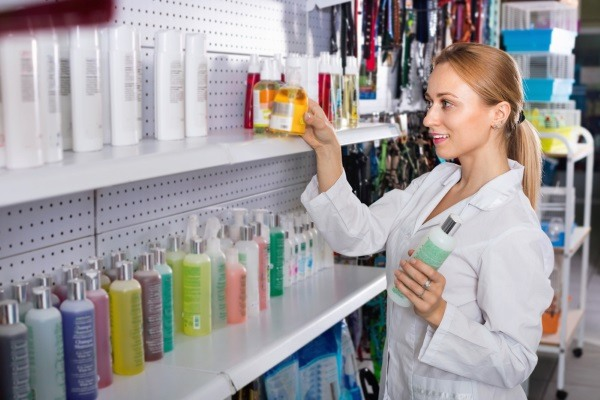 Veterinary picking a pet washing solution from a shelf for a client.