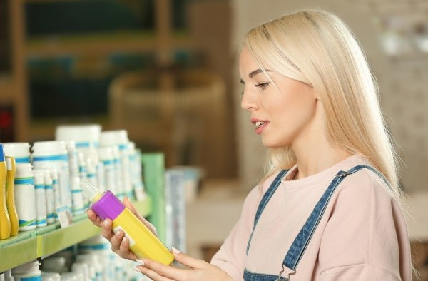 Person reading the label on a shampoo bottle before buying