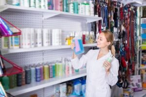 Smiling female veterinary picking a good shampoo from the shelf of a pet store